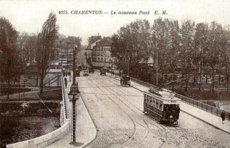 Le pont de Charenton vu d'un immeuble de Maisons-Alfort. Carte postale non datée que l'on peut situer dans les années vingt. Cette perspective avait peu changé entre le début du 20e siècle et les années cinquante. Dans le fond, on aperçoit Charenton - à gauche - et Saint-Maurice - à droite - séparés par la rue du Petit pont et, dans son prolongement, la rue de Saint-Mandé (l'actuelle rue du Maréchal de Lattre de Tassigny) qui monte vers le plateau de Gravelle. A mi-chemin du pont, au niveau du parapet, on distingue les escaliers qui permettaient alors de se rendre aux embarcadères des bateaux-mouches et aux promenades au calme entre Marne et canal. Ces escaliers (aux marches en bois à claires voies) qui existaient de chaque côté du pont ont fait place à des rampes d'accès ou de sortie de l'autoroute interdites aux piétons. Quel mépris pour ces derniers!